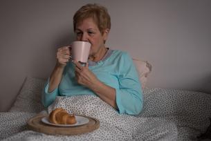 Senior woman having coffee and breakfast in bedroomの写真素材 [FYI02243135]