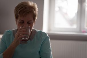 Senior woman having glass of waterの写真素材 [FYI02243155]