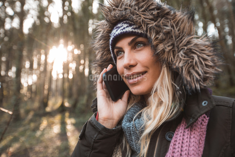 Woman talking on mobile phone in forestの写真素材 [FYI02243168]