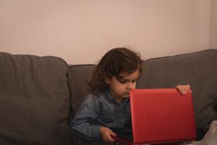 Little girl using laptop in living roomの写真素材 [FYI02243174]