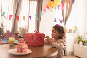 Little girl looking at gift box in living roomの写真素材 [FYI02243195]