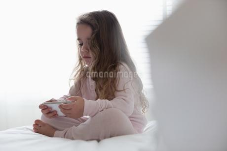 Little girl using mobile phone in bedroomの写真素材 [FYI02243196]