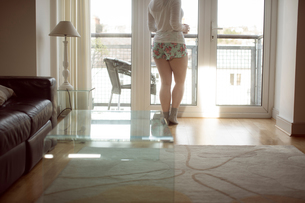 Woman looking through window at homeの写真素材 [FYI02243206]