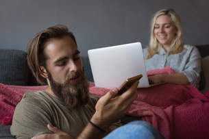 Man talking on mobile phone while woman using laptop in living roomの写真素材 [FYI02243210]