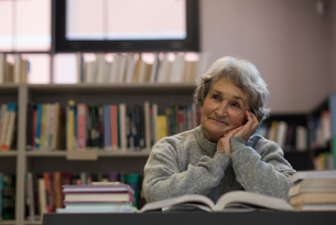 Senior woman smiling in libraryの写真素材 [FYI02243221]