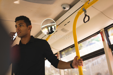 Businessman talking on mobile phone while travelling in busの写真素材 [FYI02243239]