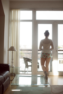 Woman looking through window at homeの写真素材 [FYI02243258]