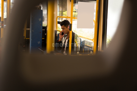 Businessman taking on mobile phone while travelling in busの写真素材 [FYI02243277]