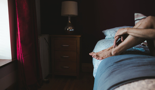 Woman relaxing on a bed in bedroomの写真素材 [FYI02243304]