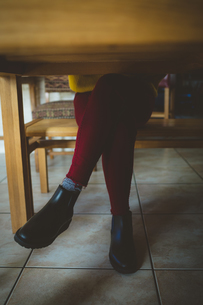 Woman sitting with legs crossed at knee in living roomの写真素材 [FYI02243333]