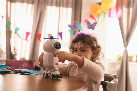 Little girl playing with robot toy in living roomの写真素材 [FYI02243364]