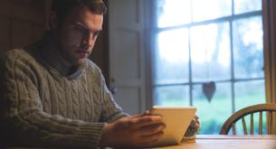 Man using digital tablet at homeの写真素材 [FYI02243366]