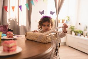 Little girl opening gift box in living roomの写真素材 [FYI02243372]