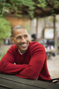 A man in a red jumper seated at a bench, smiling.の写真素材 [FYI02243428]