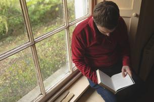 Man reading a book near windowの写真素材 [FYI02243456]