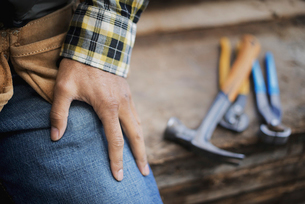 Man at a workbench, and tools lined up on a plank of wood.の写真素材 [FYI02243526]