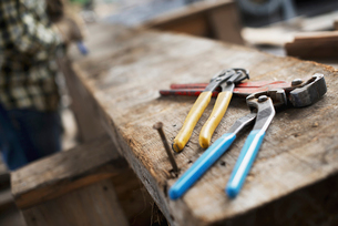 Man at a workbench, and tools lined up on a plank of wood.の写真素材 [FYI02243560]
