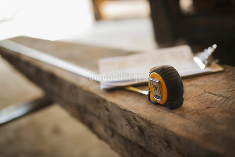 Recycled plank of wood, measuring tape and a clipboardの写真素材 [FYI02243571]
