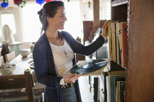 A woman in an antique storwith objects and vinyl recordsの写真素材 [FYI02243590]