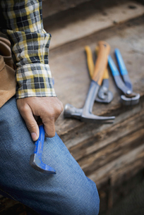Man at a workbench, and tools lined up on a plank of wood.の写真素材 [FYI02243615]