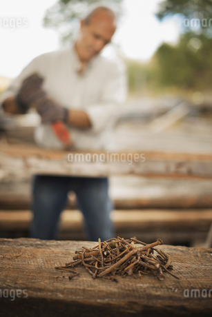 A man Using pliers to move nails from reclaimed timber.の写真素材 [FYI02243621]