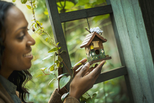 A woman holding a small painted bird house in an enclosure.の写真素材 [FYI02243644]
