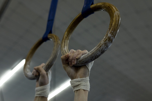 Woman hanging on gym ring at fitness studioの写真素材 [FYI02243934]