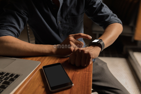 Businessman using his smartwatch in the coffee shopの写真素材 [FYI02243985]