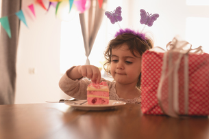 Little girl having cake in living roomの写真素材 [FYI02244028]