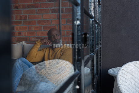 Senior man relaxing on sofa at homeの写真素材 [FYI02244039]