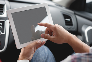Man using digital tablet in carの写真素材 [FYI02244055]