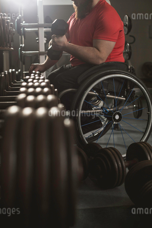 Handicapped man on wheelchair lifting dumbbell from rackの写真素材 [FYI02244058]