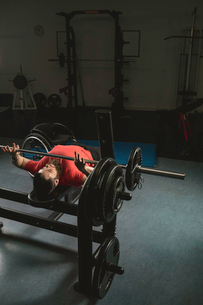 Handicapped man doing barbell bench pressing while exercisingの写真素材 [FYI02244077]