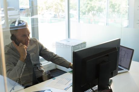 Businessman talking on telephone at deskの写真素材 [FYI02244159]