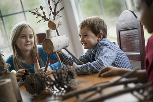 Three children A twig reindeer with branches and twigs to make objects.の写真素材 [FYI02244183]