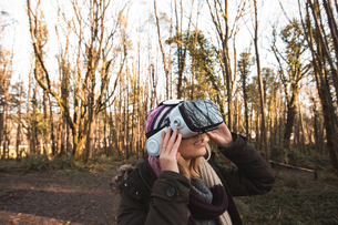Woman using virtual reality headset in the forestの写真素材 [FYI02244192]