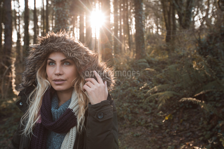 Woman in hoodie standing at forestの写真素材 [FYI02244255]