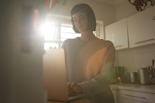 Woman using laptop in kitchen at homeの写真素材 [FYI02244264]