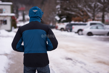 Man standing with hands in pocket on snowy streetの写真素材 [FYI02244288]