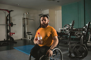 Handicapped man on wheelchair with water bottle in gymの写真素材 [FYI02244291]