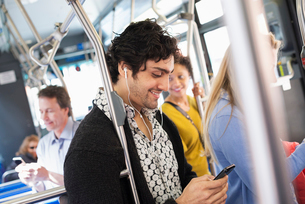 A young man checking his cell phone travelling on a bus.の写真素材 [FYI02244380]