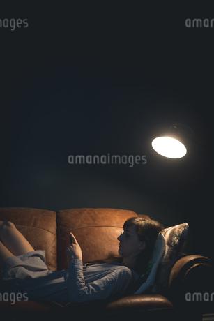 Woman using mobile phone while lying on sofaの写真素材 [FYI02244382]