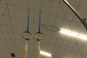 Woman hanging on gym ring at fitness studioの写真素材 [FYI02244423]