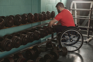 Handicapped man on wheelchair lifting dumbbell from rackの写真素材 [FYI02244425]