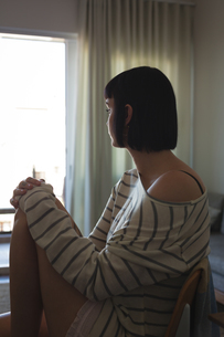Worried woman sitting on sofa in living roomの写真素材 [FYI02244448]