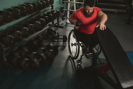 Handicapped man on wheelchair working out with dumbbellの写真素材 [FYI02244463]