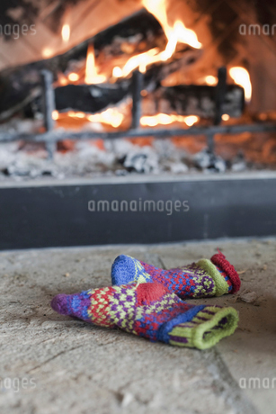 A log fire in a hearth. Patterned knitted woollen gloves.の写真素材 [FYI02244498]