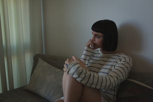 Worried woman sitting on sofa in living roomの写真素材 [FYI02244531]