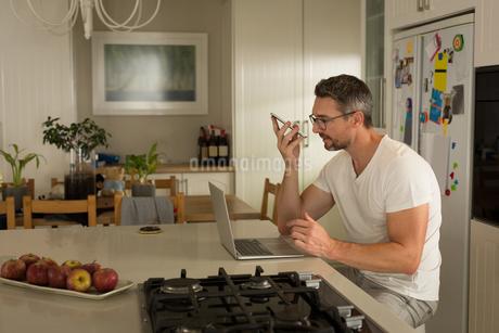 Man using laptop while talking on mobile phoneの写真素材 [FYI02244577]
