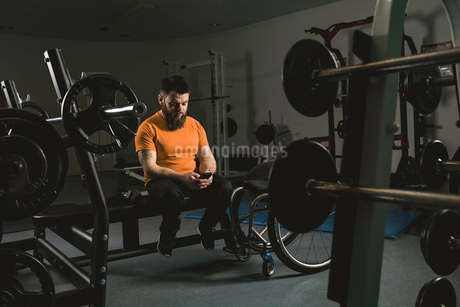 Handicapped man using mobile phone on bench pressの写真素材 [FYI02244591]